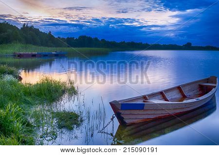 Travel Destinations Concepts. Tranquil and Peaceful Picturesque Landscape of The Strusto Lake with Wooden Boat at Foreground. Lake is a Part of National Braslav Lakes Reserve. Horizontal Image Composition