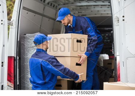 Two Young Male Movers Carrying Cardboard Box From Truck