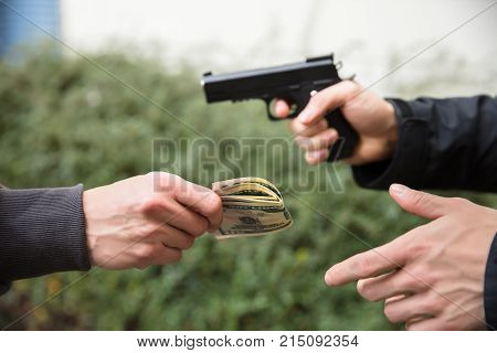 Close-up Of Robber's Hand With Gun Threatening Someone To Give Money
