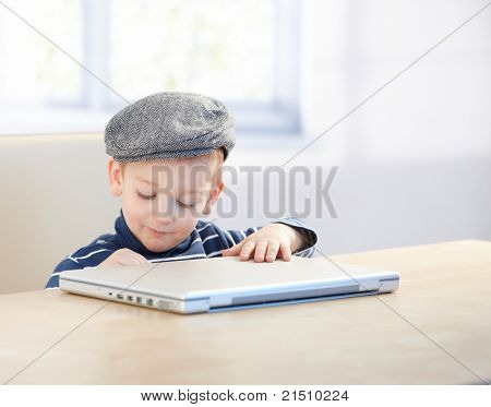 Sweet little kid sitting at table, wearing cap, playing with laptop.?