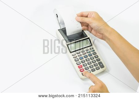 Left hand presses the keys of the printing calculator the right hand takes out a paper check