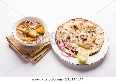 potato curry or aloo masala or alu masala with green peas, served with indian bread or roti or naan