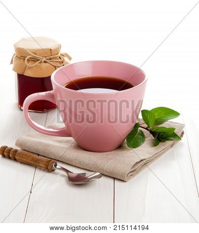 pink tea cup on white wooden background