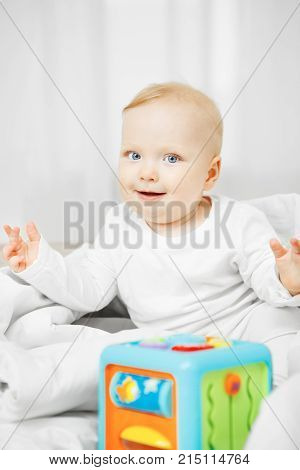 Adorable playful baby with blond hair, big light eyes sits on bed with cubic toy for mental development dressed in white crawlers and spreads hand with smile.