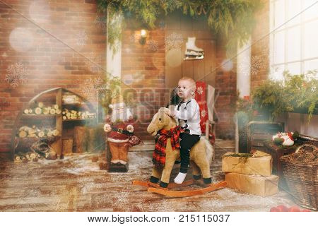 Playful Happy Cute Little Child Boy Sitting On Rocking Horse In Decorated New Year Room With Santa A