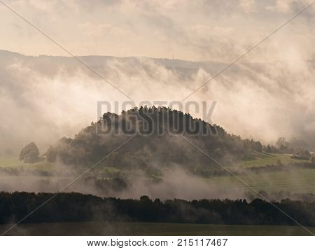 Outlines Of Forest Hills Hidden In Thick Mist. Unclear View To Contours Of Hills