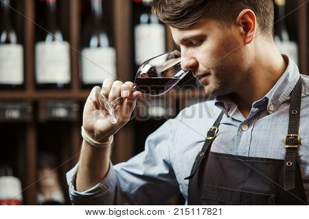 Sommelier smelling flavor of red wine in bokal on background of shelves with bottles in cellar. Male appreciating color, quality and sediments of drink. Professional degustation expert in winemaking. poster