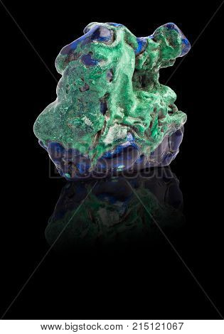 Blue and green Azurite gemstone with ground reflection on the black background