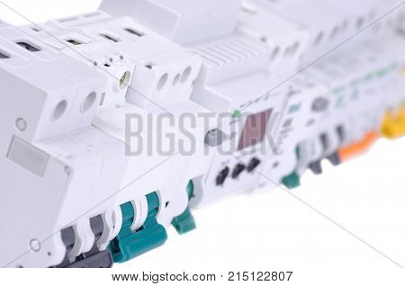 Various miniature circuit breakers and other devices on white background.