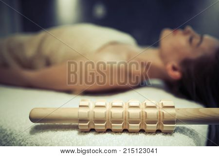 Masseuse lying on massage bed with massage roller by her side