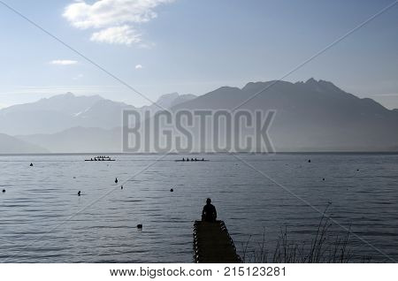 Man Sitting On Pontoon In Front Of Lake Annecy
