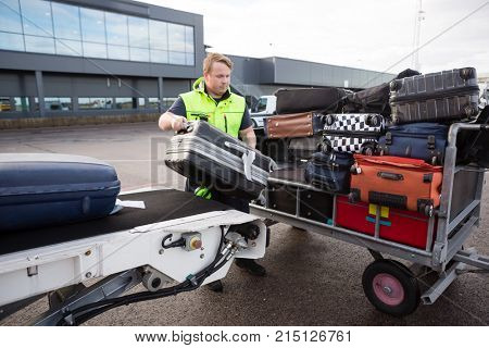 Worker Stacking Luggage On Trailer From Conveyor On Runway
