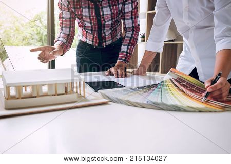 Two interior design or graphic designer at work on project of architecture drawing with work tools and color swatches colour chart color samples for selection renovation and technology concept.