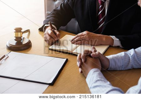 Close up of gavel Male lawyer or judge Consult with client and working with Law book report the case on table in modern office Law and justice concept.