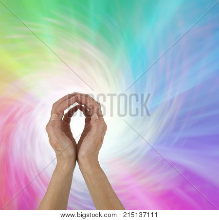 Rainbow Spiral Energy healing hands - female  hands with fingertips touching on a spiralling rainbow coloured background and a ball of white light plus copy space all around