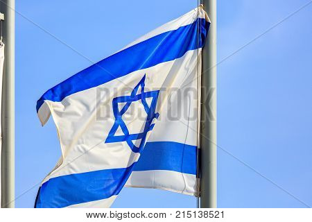Blue and white flag of Israel on strong wind