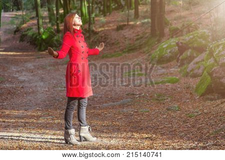 Woman enjoying the warmth of winter sunlight alone on forest park path with arms open receiving rays of light, wearing a red long coat or overcoat