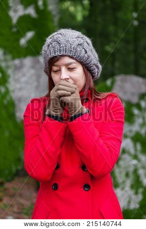 Young woman shivering with cold and blowing hot air to the hands on a forest wearing a red long coat or overcoat, a beanie and gloves during winter