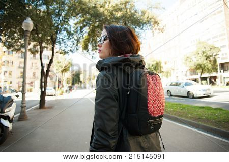 Young female tourist with backpack walking in sunny day in Barcelona city. Woman travelling and exploring Spain