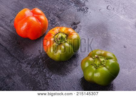 Appetizing, juicy, Bulgarian pepper, decomposed orange and green, mature, and half-ripe, on a black background
