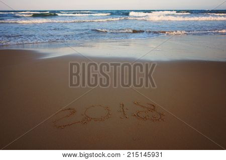 New Year 2018 is written on the sand on the beach with an incoming foaming wave, horizontal.