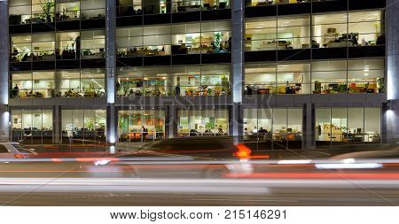 Night street with cars and office building fasade in Moscow, Russia. Lighting windows and working people.