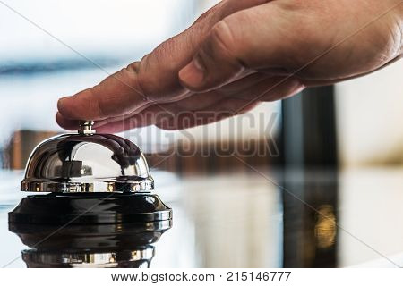 hand presses the service bell on reception in hotel or restaurant
