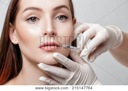 Portrait of beautiful woman getting injection on lips. beauty injections and cosmetology