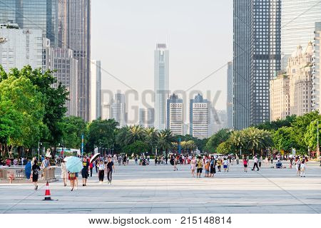 Asian Tourists Walking In A City Park Among Modern Buildings