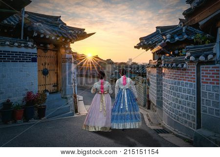 Back of two women wearing hanbok walking through the traditional style houses of Bukchon Hanok Village in Seoul South Korea.