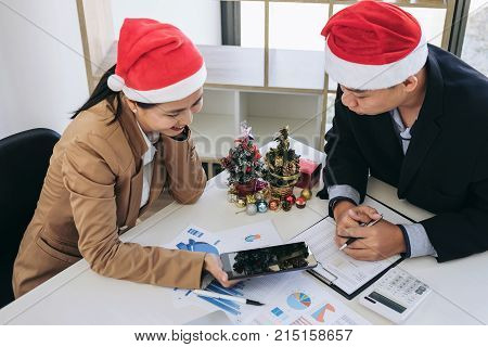 Merry Christmas and Happy New Year Young business team are celebrating holiday in workplace are sitting in Santa hats and they looking travel with the colleagues Working in the last month of year.