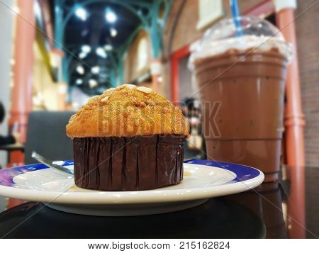 Fresh muffin almond on white ceramic plate with ice chocolate with milk on to in local cafe