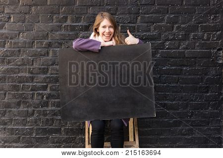 background, arts and crafts, emotions concept. fairhaired young woman is loughing and giving thumb up, she has adorable smile and ring in the thumb, and blackboard on her knees