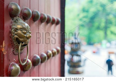 Chinese door knocker on a red opened gate with outdoor blur view in the background, DuJianYan, China