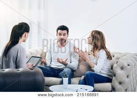 Heated argument. Unhappy irritated young couple discussing their problem and having disagreements with each other while visiting a family psychologist