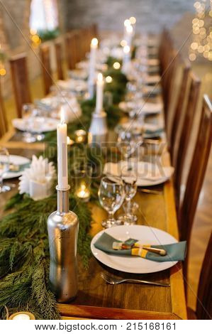 wedding decor, interior, illumination concept. close up of served holiday table with candles in original holders that looks like bottles, among them there are fresh branches of conifer trees