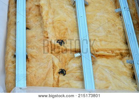 Exterior house wall heat insulation with mineral wool closeup, unfinished result of installing insulate panels