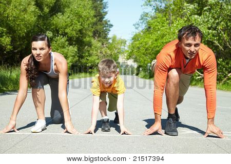 Portrait of family of three standing on start before running