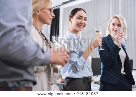 partial view of business colleagues with glasses of champagne having celebration in office