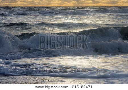 Small waves in a troubled sea roll on the shore with foam and spray under the cloudy sky and the rays of the sun