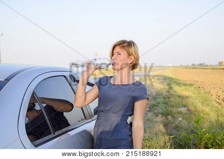 Slavyansk-on-Kuban Russia - September 17 2017: The girl quenches his thirst. Blonde drinks water from a plastic bottle.
