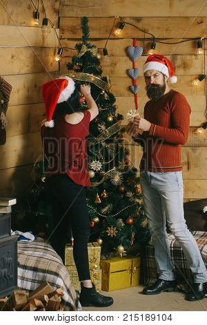 New year guy and girl decorate Christmas tree. Winter holiday and celebration. Couple in love in santa hat family. Xmas party preparation. Christmas man and woman couple at present box.