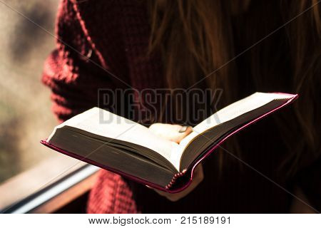 a woman holding and reading bible inspiration