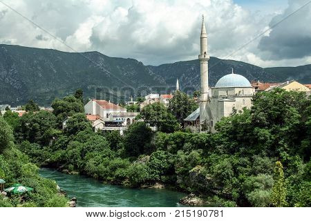 Karadjozbegova mosque seen from its opposite bank of the river Neretva in Mostar Bosnia and Herzegovina. It is one of the landmarks of the city.