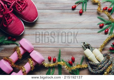 Fitness healthy and active lifestyles greeting card concept dumbbells sport shoes skipping rope or jump rope with Christmas decoration on wood background. Exercise Merry Christmas Healthy concept