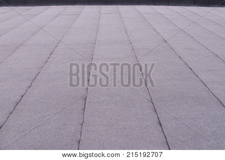 Flat surfaced roof coating. Heating and melting bitumen roofing felt background pattern