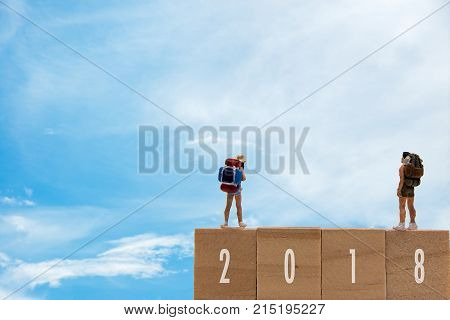 Miniature group traveler standing on wooden 2018 with new year blue sky background. Holiday Concept