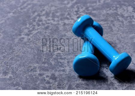 Barbells Placed Crosswise In Closeup. Dumbbells Made Of Cyan Plastic