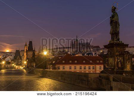 Charles bridge and Prague Castle in night. Gas lamps illuminating cobblestones of Charles bridge in Prague Czech Republic.