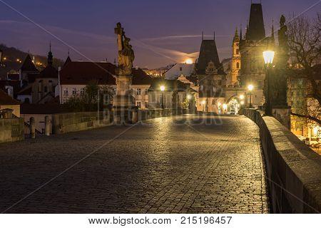 Charles bridge in morning twilight. Gas lamps illuminating cobblestones of Charles bridge in Prague Czech Republic